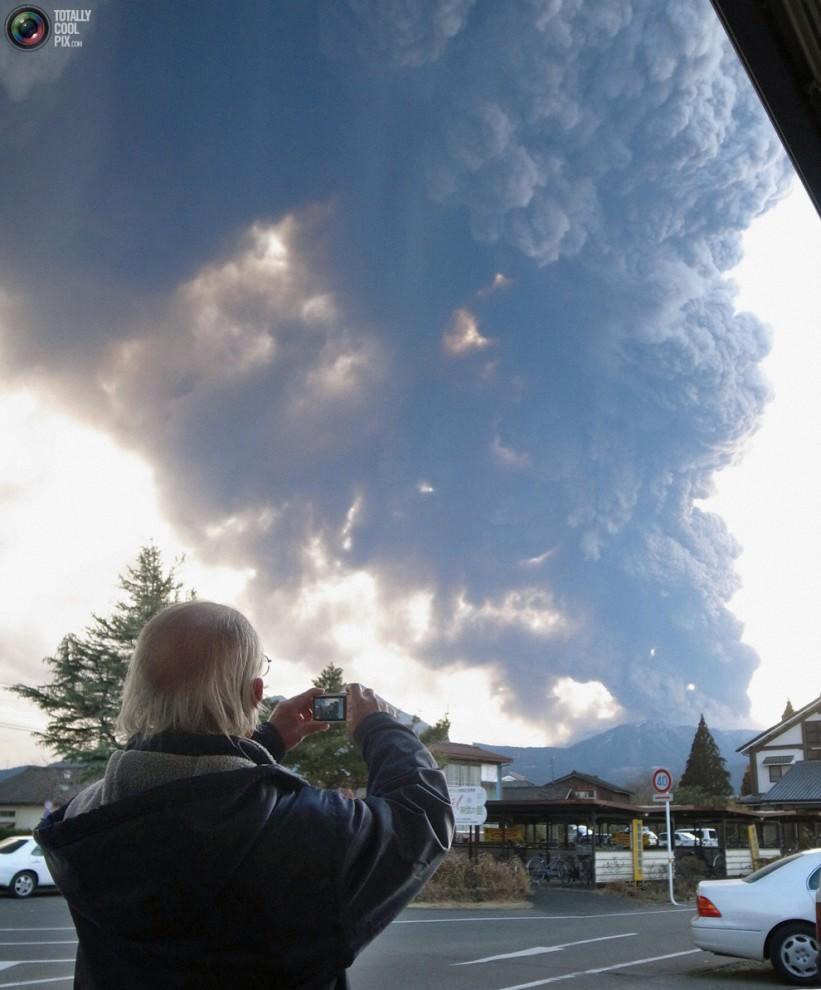 Человек делает снимок извержения вулкана