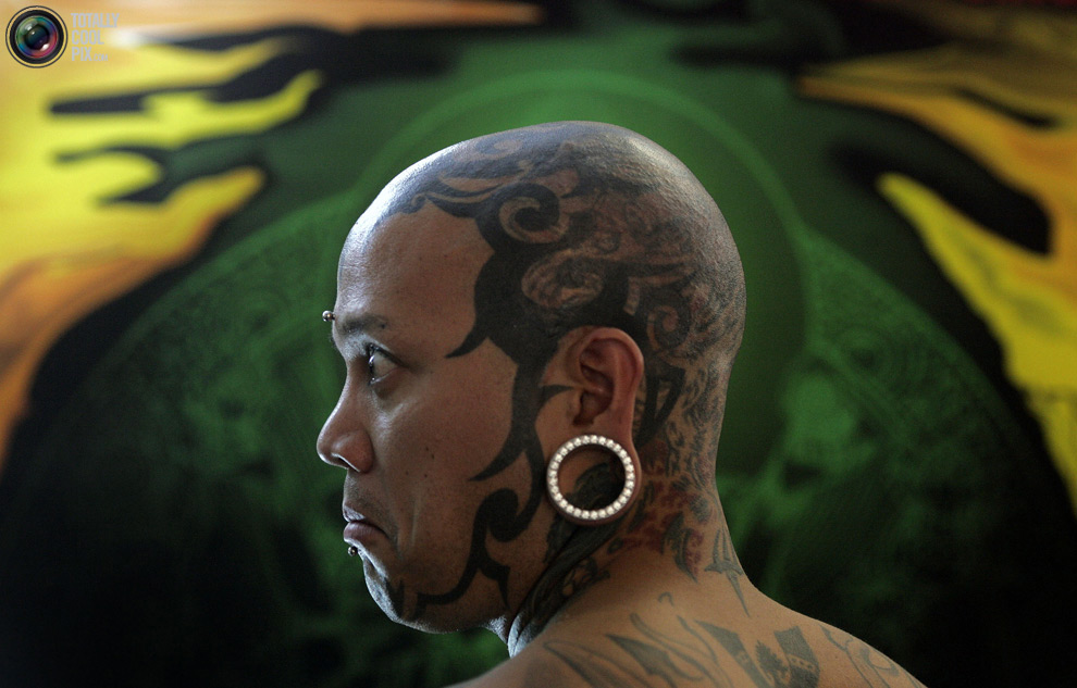 Мужчина демонстирует татуировки на голове на лондонской Тату-Конвенции