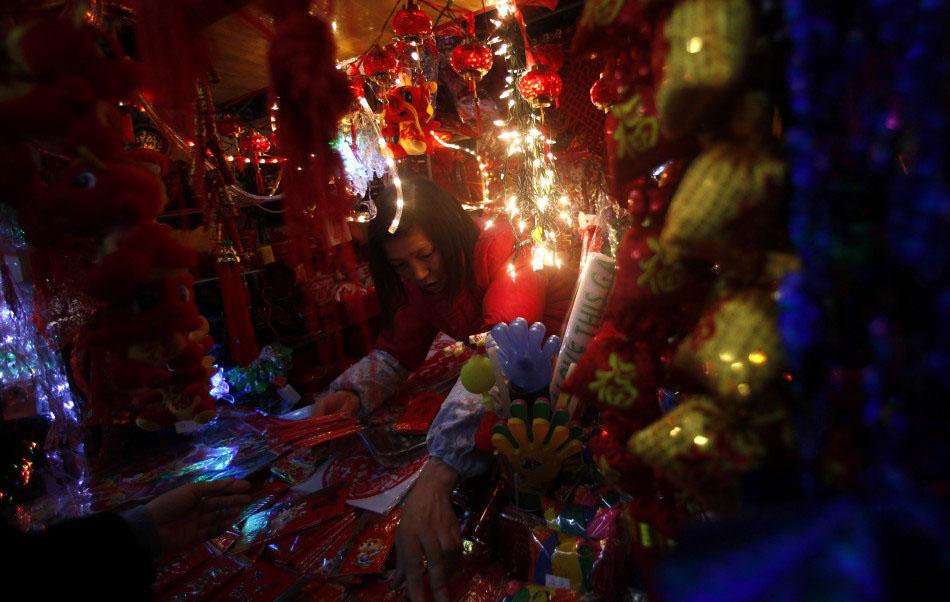 217615 a vendor stands inside her shop selling chinese new year products at a Подготовка к китайскому Новому году Дракона