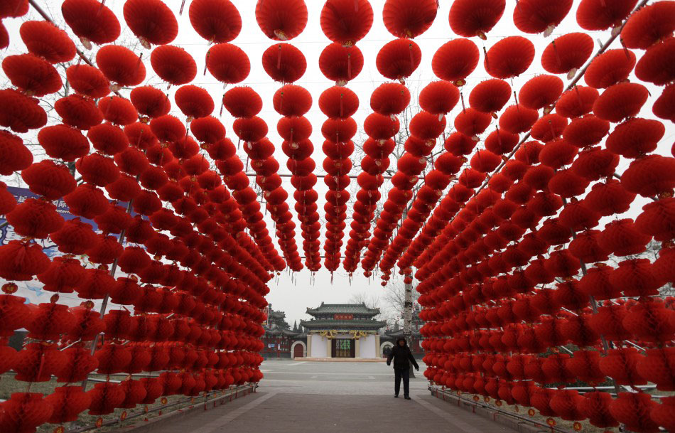 217618 a woman walks past red lanterns which were put up as decoration for an Подготовка к китайскому Новому году Дракона