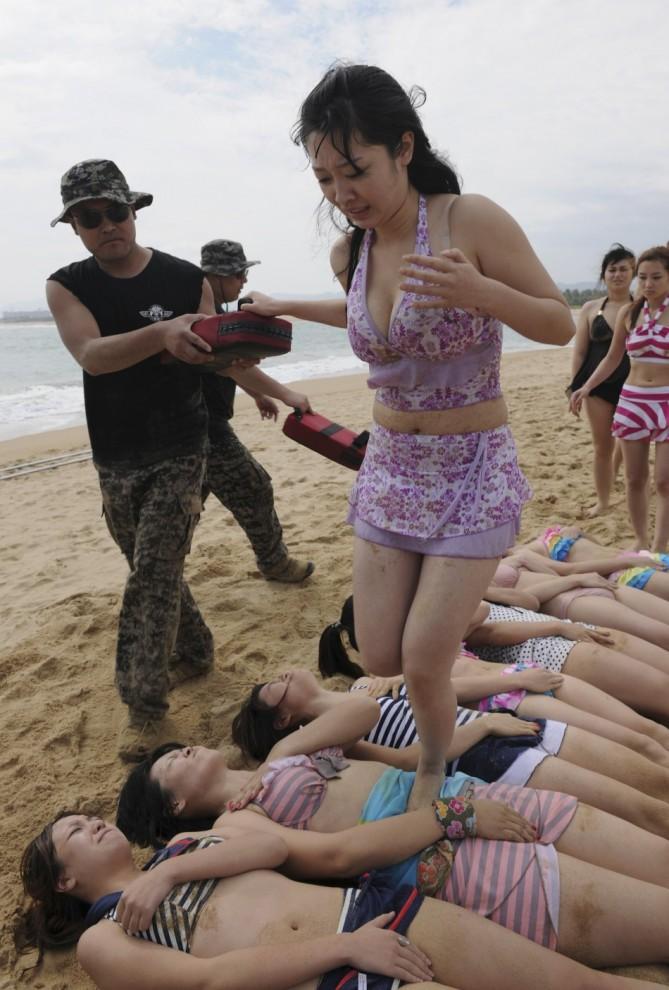 7. …затем девушки ходят по животам своих коллег. Лежащие девушки должны напрячь пресс как можно сильнее. Потом команды меняются местами. (Reuters)