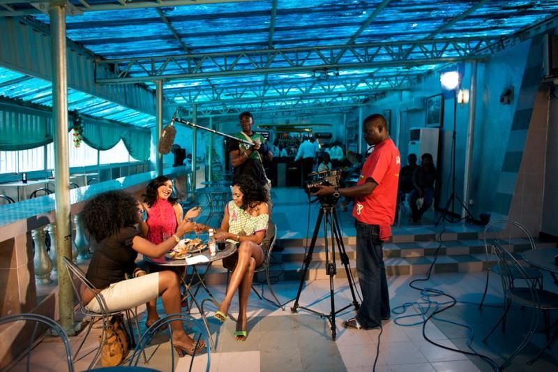 . Хотя фильмы в Нигерии снимались и до 1960 года, рост доступной цифровой съемки и технологии редактирования стимулировал рост данной отрасли. На фото: Актер Нонсо Диоби и актриса Тонто Дике репетируют на съемочной площадке фильма «Стриптизерши». (© Guy Calaf/LUZphoto)