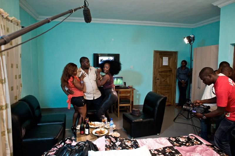 9. Звезды Нолливуда, снимающиеся в серьезных фильмах, зарабатывают хорошие гонорары — до 10 тысяч в месяц. Это очень большие деньги для Нигерии. Но и работать им приходится помногу: рабочий день начинается еще до рассвета и заканчивается с заходом солнца. На фото: Актриса Халима (в оранжевом) в сцене из фильма «Стриптизерши». (© Guy Calaf)