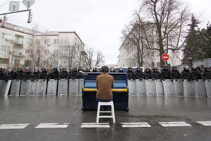 1. Мужчина играет на пианино для милиции. Киев, 2013 год. Ранее в декабре прошлого года украинцы приняли участие в крупнейшей с 2004 года акции протеста.