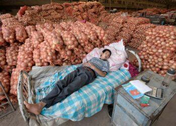7. Продавец спит рядом с мешками лука в ожидании покупателей на оптовом рынке в Тайюане, провинция Шаньси, Китай. (Jon Woo/Reuters)