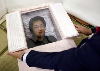 1. Норияки Ивасима позирует в гробу.