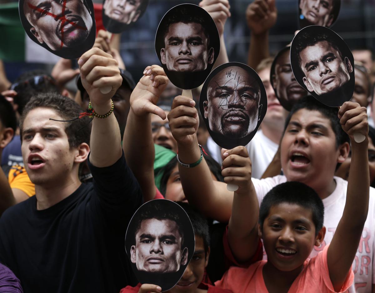 10. Болельщики вышли на площадь Таймс сквер чтобы поддержать боксеров Флойд Мэйвезера и Маркос Рене Майдана Нью Йорк 13 сентября 2014. Площадь Таймс сквер в Нью Йорке