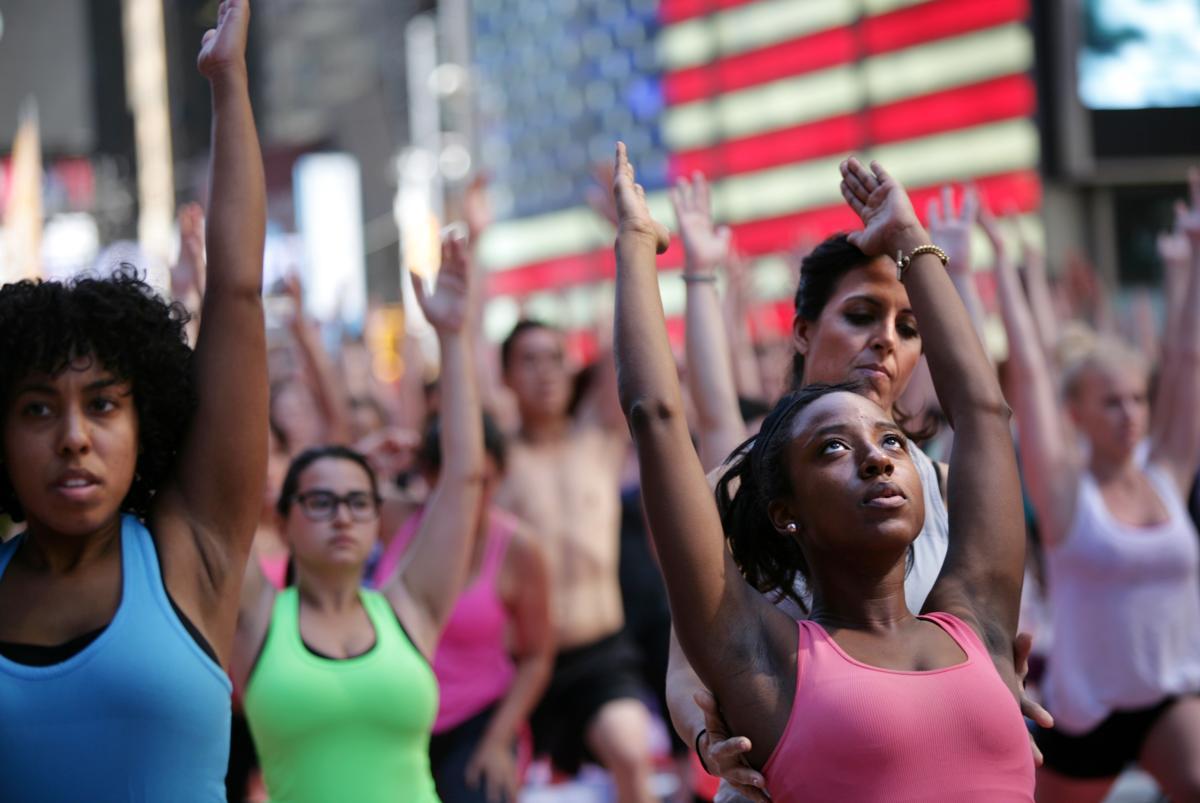 12. Около 8000 человек приветствуют солнце в день летнего солнцестояния 21 июня 2014. Площадь Таймс сквер в Нью Йорке