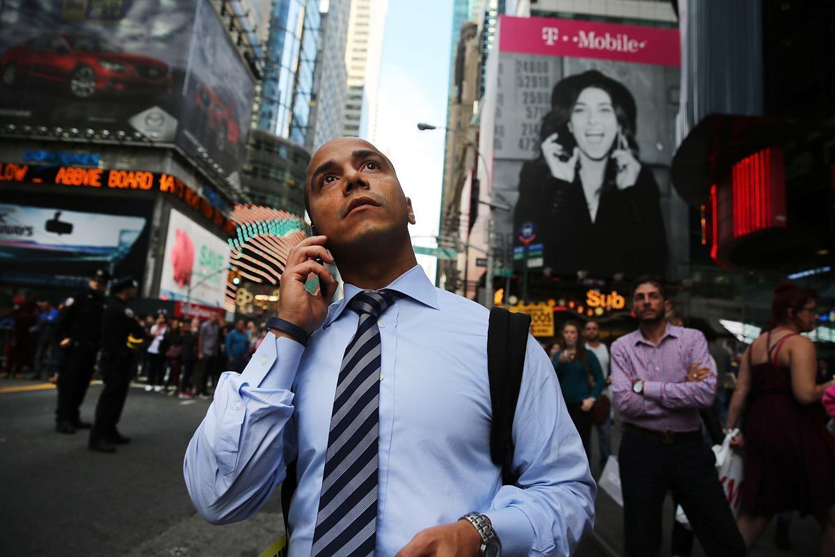 14. Мужчина стоит на Таймс сквер неподалеку от музея мадам Тюссо 16 октября 2014. Площадь Таймс сквер в Нью Йорке