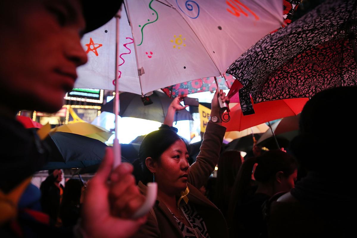 20. Люди с зонтами во время проведения демонстрации в поддержку жителей борющихся за демократию в Гонконге Площадь Таймс сквер в Нью Йорке