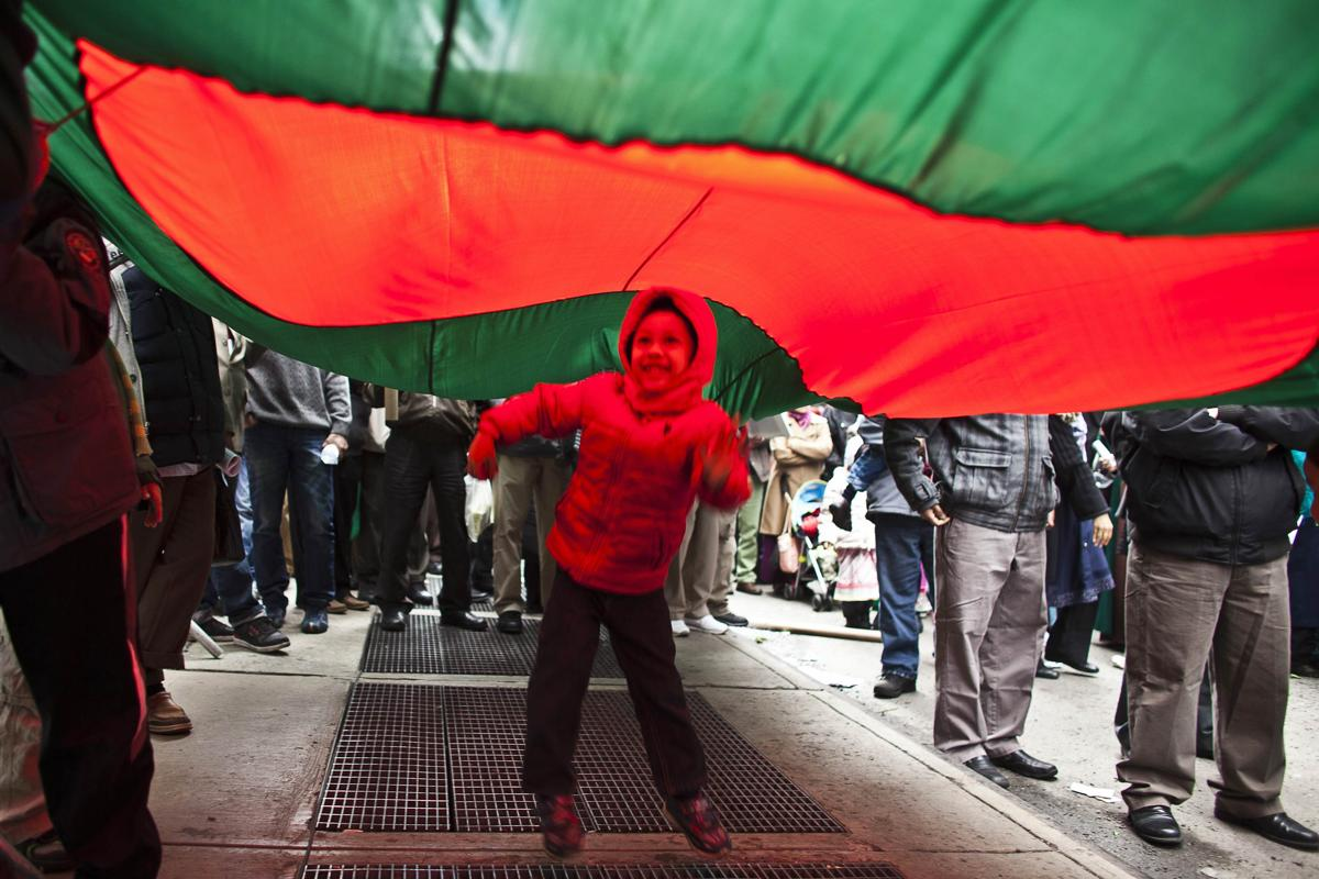 21. Мальчик прячется под флагом во время демонстрации американских мусульман против правительства Бангладеш Нью Йорк 13 апреля 2013. Площадь Таймс сквер в Нью Йорке