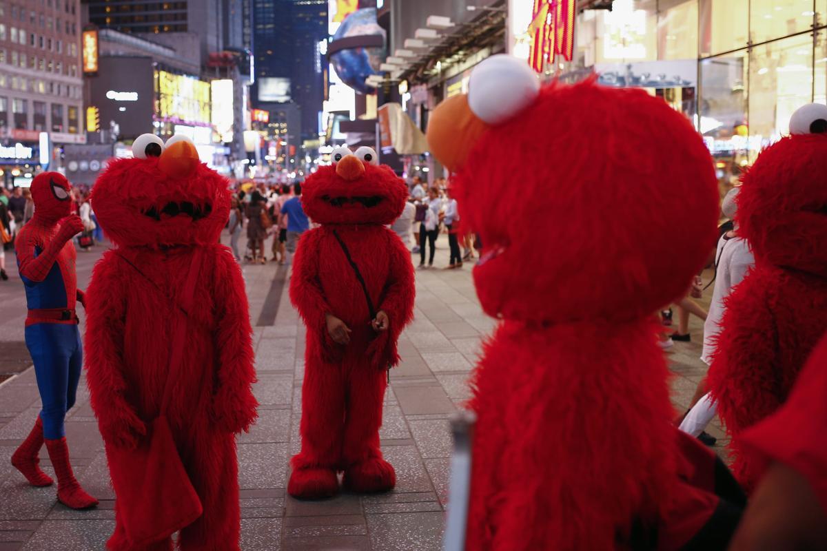 22. Люди в костюмах мультяшных героев фотографируются с туристами на Таймс сквер 30 июля 2014. Площадь Таймс сквер в Нью Йорке