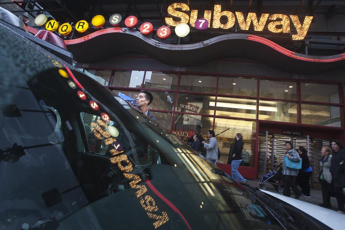 3. В лобовом стекле полицейской машины отражается светящаяся вывеска Таймс сквер Нью Йорк 25 сентября 2014. Площадь Таймс сквер в Нью Йорке