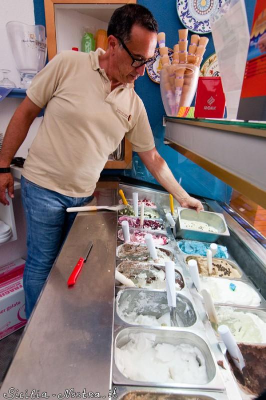 Джузеппе ставит контейнер с только что сделанным мороженым в витрину.