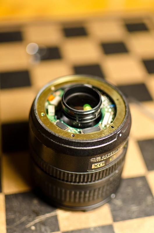 Объектив со снятым байонетом. Контакты байонета подключены гибким кабелем в размъе на плате контроллера, коричневая пластиковая скоба на нем со стороны шлейфа аккуратно поднимается вверх, и кабель освобождается.