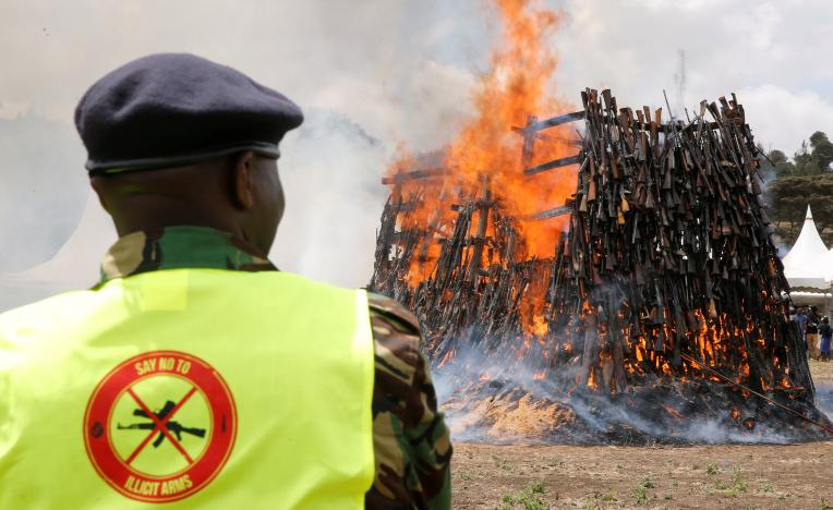 A policeman watches as an assortment of 5250 illicit firearms and small weapons, recovered during various security operations burns during its destruction in Ngong hills near Kenya's capital Nairobi