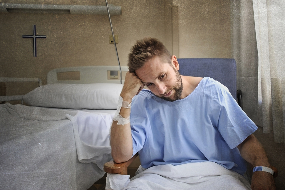 young injured man in hospital room sitting alone in pain worried