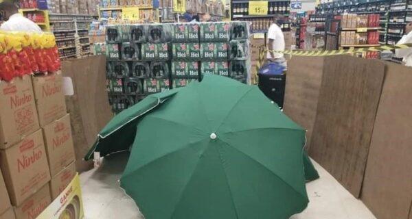 Когда сотрудник магазина умер, его прикрыли зонтами и продолжили работать