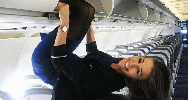 Стюардесса в мини-юбке закрыла багажные полки, повиснув вниз головой и раздвинув ноги