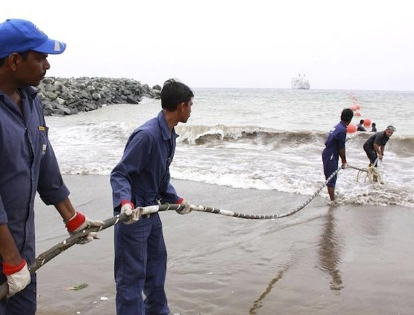 Alcatel lucent contractors lay the teams fibre optic cable on the fujairah shore end in the uae